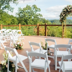 Stunning ceremony space at The Magnolia venue overlooking the Pigeon Forge mountains anchored by a gold arch covered in lush greenery and roses by LB Floral