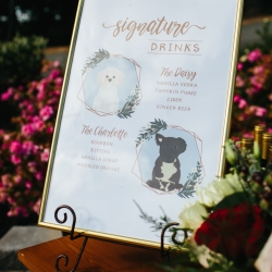 Signature cocktails custom sign features the bride and grooms beloved dogs during a fall wedding coordinated by Magnificent Moments Weddings