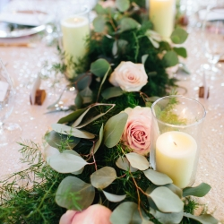 Lush greenery garland accented with blush roses by LB Florals are accented by white pillar candles to create a romantic feel for a mountain top wedding in Tennessee at The Magnolia