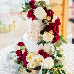 Stunning cake from Magpies Bakery features white detail icing and a cascade of white and red roses