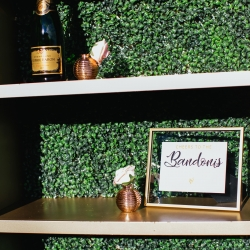 Custom bookshelf features greenery backing and cute name sign for a fall wedding coordinated by Magnificent Moments Weddings