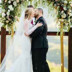 Bride and groom share a kiss under a stunning gold arch covered in roses by LB Florals