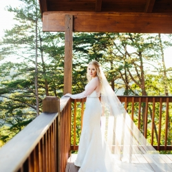 Bride shows of her breathtaking veil while overlooking the Pigeon Forge Mountains during her wedding at The Magnolia