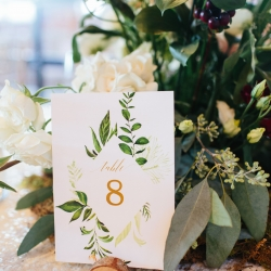 Custom table numbers feature leafy green patterns set atop stunning linens from BBJ all coordinated by Magnificent Moments Weddings