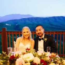 Bride and groom share a smile with Alex Bee Photography during their wedding reception that overlooked the stunning Tennessee mountains