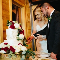 Bride and groom cut their stunning cake by Magpies Bakery with cascading white and ride roses
