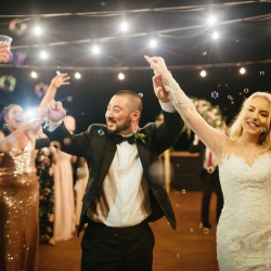 Bride and groom exit through a sea of bubbles at the end of their mountain top wedding coordinated by Magnificent Moments Weddings