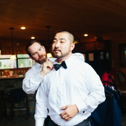 Groom prepares for his wedding by putting on a bow tie captured by Alex Bee Photography