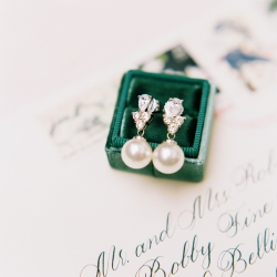 Ally and Bobby Photography captures a detail shot of bridal earrings in a stunning emerald box for a winter wedding at Carmel Country Club