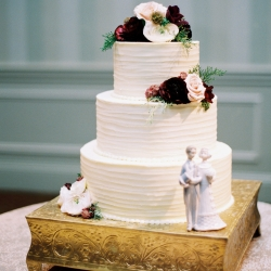 Simple white cake created by Carmel Country Club catering is accent by burgundy flowers and set a top a gold cake stand
