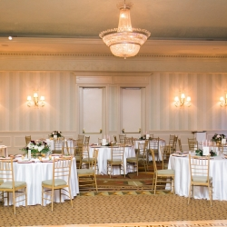 Carmel Country Club serves as the perfect backdrop for a winter wedding reception featuring gold and emerald green accents planned and designed by Magnificent Moments Weddings