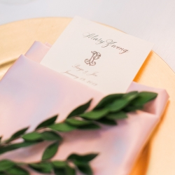 Menu card for Carmel Country Club wedding is tucked delticatly into a blush napkins set atop a stunning gold charger