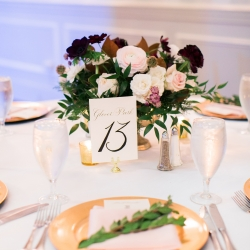 Magnificent Moments Weddings designed a stunning tablescape featuring gold charges accented with lush greenery and compote vases filled with color flowers created by Jimmy Blooms