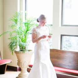 Bride reads a sweet letter from her groom as she prepares for her wedding ceremony at St Gabriel's Catholic Church