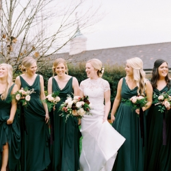 Bride poses with her bridesmaids who show off stunning emerald green full length gowns