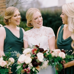 Bride poses with her bridesmaids holding a stunning bridal bouquet featuring delicate white roses and deep burgundy accents all surrounded by lush greenery
