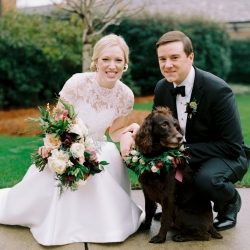 Bride and groom pose with their dog who is wearing a delicate floral collar created by Jimmy Blooms