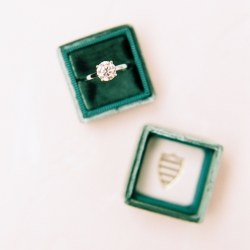 Solitaire engagement ring is accent by a green velvet box all captured by Ally and Bobby Photography