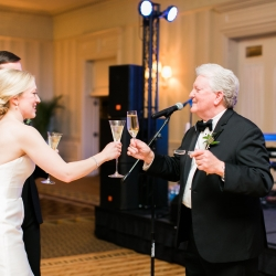 Bride and groom share a toast with her father during their winter wedding planned by Magnificent Moments Weddings