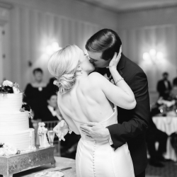 Bride and groom share a kiss during their cake cutting captured by Ally and Bobby Photography