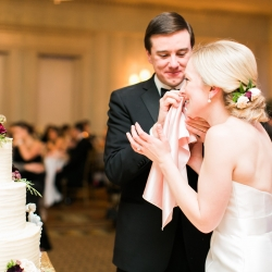 Groom wipes frosting from his brides face as they taste their wedding cake created by Carmel Country Club during their winter wedding in Charlotte, North Carolina