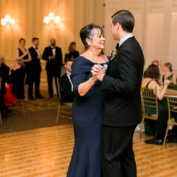 Groom shares a dance with his mother to music provided by The Business band during their winter wedding at Carmel Country Club