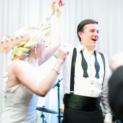 Bride and groom enjoy a moment dancing with their band The Business during their wedding reception planned by Magnificent Moments Weddings