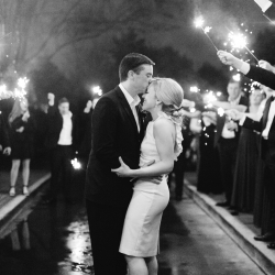 Bride and groom share a kiss under sparklers as they exit their wedding reception at Carmel Country Club in Charlotte, North Carolina