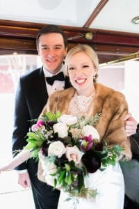 Bride and groom pose on a vintage trolley during their winter wedding in Charlotte, North Carolina