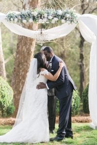 Bride and groom kiss during wedding ceremony coordinated by Magnificent Moments Weddings at Vesuvius Vineyards