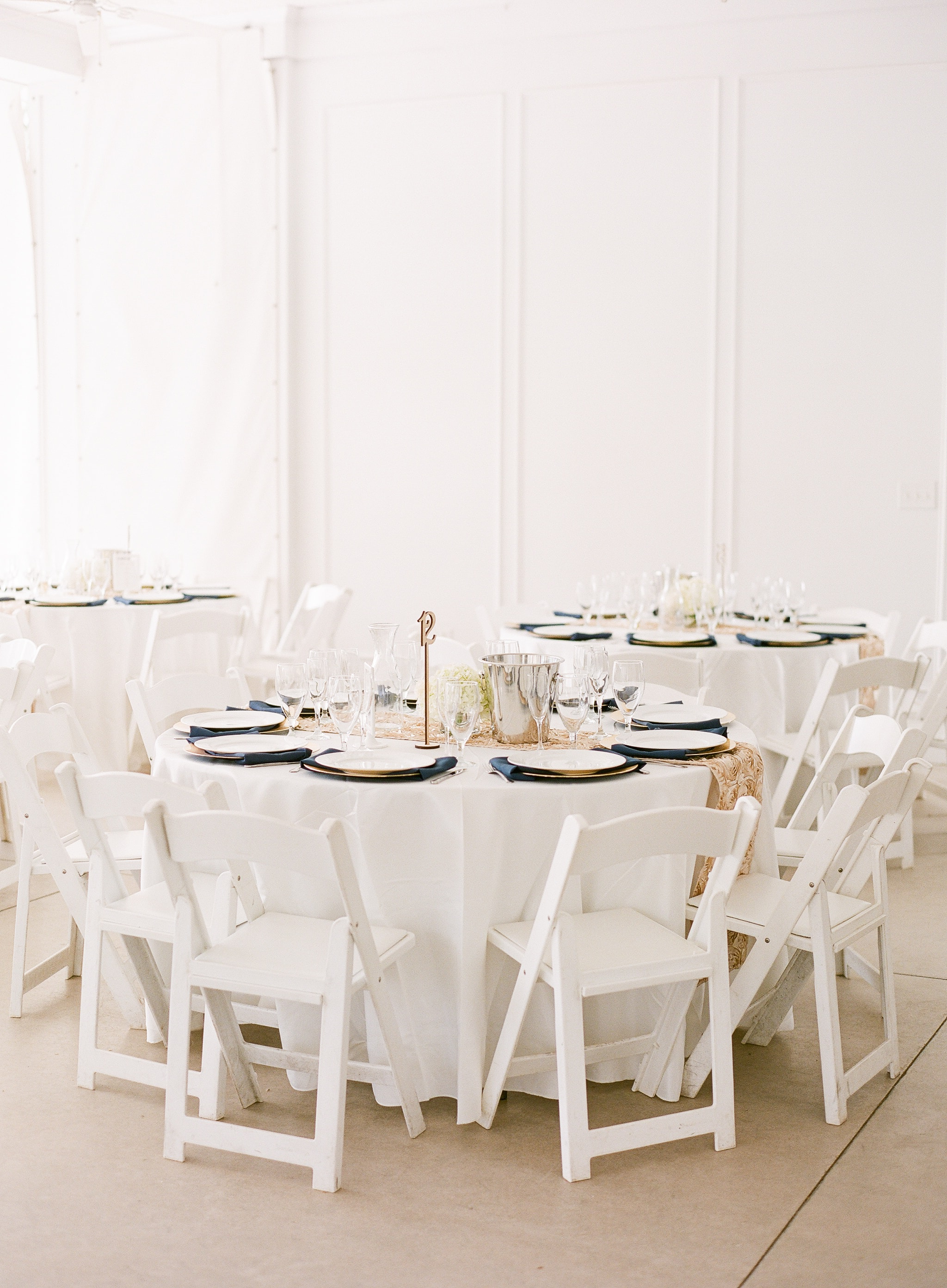 Reception tables set with white linens and accented with navy napkins for a wedding reception at Vesuvius Vineyards coordinated by Magnificent Moments Weddings