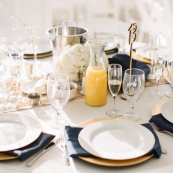 Reception table set with white linens. gold chargers and navy napkins create a stunning reception space at Vesuvius Vineyards coordinated by Magnificent Moments Weddings