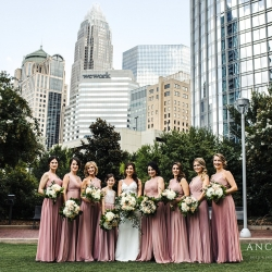 Anchor and Veil Photography captures a bride and her bridesmaids amide the city skyline of Charlotte before their summer wedding