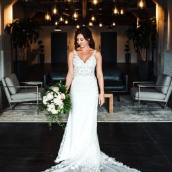 Bride shows off her stunning dress with lace train and amazing bouquet created by Midwood Flower Shop