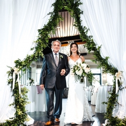 Bride escorted down the aisle by her father through a greenery lined drapery designed by Midwood Flower Shop for an Uptown Charlotte Wedding