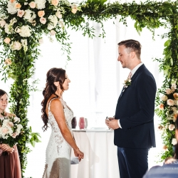 Bride and groom exchange vows they have written during their summer wedding coordinated by Magnificent Moments Weddings