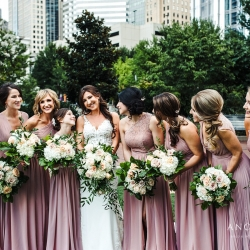 Bridesmaids show off the love as they pose with the bride amid the city skyline in Uptown Charlotte