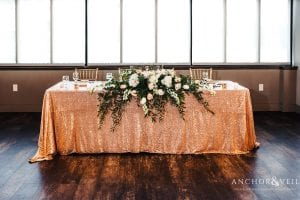 A modern head table is covered in sequins and stunning flowers from Midwood Flower Shop in Uptown Charlotte
