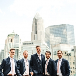 Groom poses with his groomsmen amid the Charlotte skyline before his summer wedding.