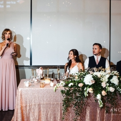 Bride and groom are all smiles as their family and friends share toasts during their wedding reception coordinated by Magnificent Moments Weddings