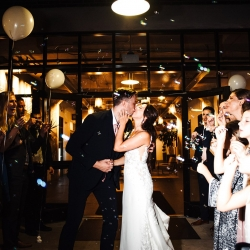 Bride and groom kiss amid a sea of bubbles and balloons all captured Anchor and Veil Photography