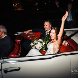 Bride and groom exit in a vintage car from their summer wedding at Terrace at Cedar Hill