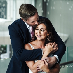 Bride and groom embrace during their summer wedding in Uptown Charlotte