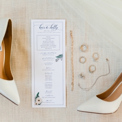 Detail shot of wedding jewelry and invitation for a Dairy Barn wedding captured by Ashley Sue Photography