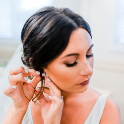 Bride puts on her earrings and shows of stunning hair and makeup by Beauty Asylum before her wedding at The Dairy Barn