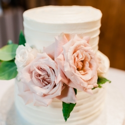 White two tier cake by Publix Bakery made special by pink roses from Wild Petals Studios