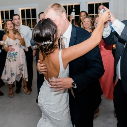 Bride and groom dance to music by Split Second Sound during their wedding reception at The Diary Barn