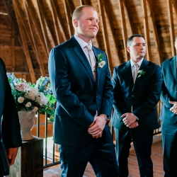 Shot of groom seeing his bride walk down the aisle during their Diary Barn ceremony captured by Ashley Sue Photography