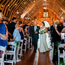 Bride being escorted down the aisle to her wedding ceremony as family and friends look on during her spring wedding at The Dairy Barn in Fort Mill, South Carolina