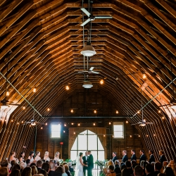 Lofted ceiling of The Dairy Barn serves as the romantic scene of a wedding ceremony coordinated by Magnificent Moments Weddings and captured by Ashley Sue Photography
